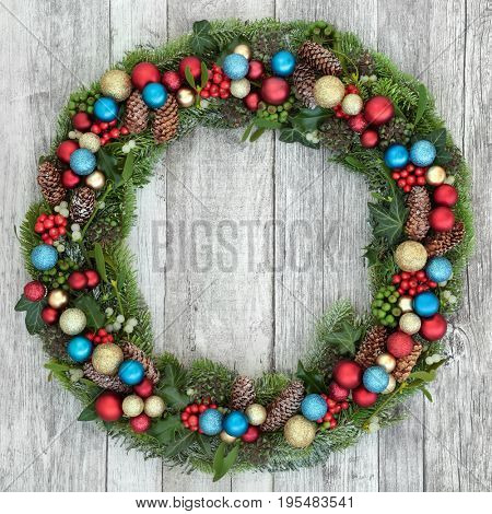 Christmas wreath decoration with red, gold and blue baubles, holly, mistletoe, fir, blue spruce, ivy and pine cones on distressed white wood background.