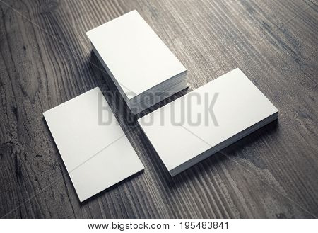Three piles of blank business cards on wood table background. Mock-up for branding identity for designers. Blank template for your design.