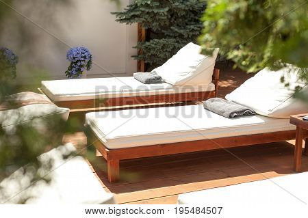 hotel rest, vacations and summer joy concept - closeup two beautiful sun loungers with cushions and towels for relaxing, leather deckchairs on wooden floor, resort entertainments, solar spa near pool