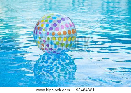 holiday lifestyle, rest and summer swimming concept - on surface of blue pool water is inflatable transparent ball decorated by multi-colored circles, entertainment in hotel or backyard of household