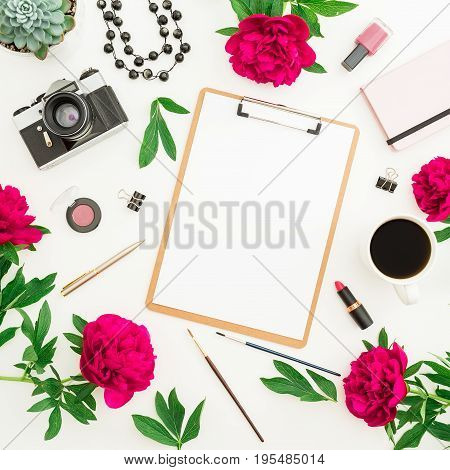 Beauty blogger or freelancer desk workspace with clipboard, notebook, retro camera, red flowers, coffee mug and accessories on white background. Flat lay, top view.