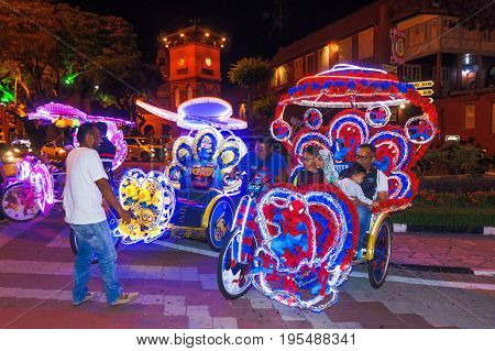 Melaka Malaysia - April 20 2017: Colourful trishaws decorated with bright multi-colour lights and cartoon pictures are ready to take passengers for sight-seeing the old town in night time.