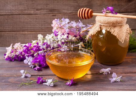 Jar of honey with wildflowers on a dark wooden background.