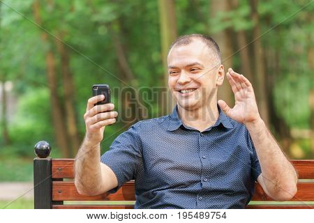 Adult Man Around 35-40 With Smile Is Talking On Video Communication By Phone At Summer Park