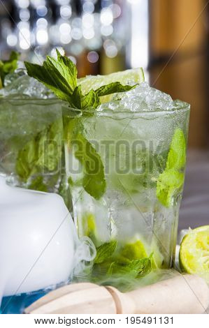 Classic mojito cocktail on the bar, with lime mint and sugar decoration