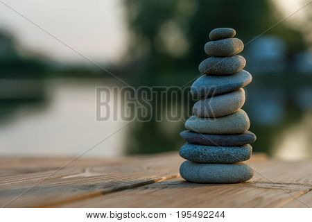Zen Balancing Pebbles Next to a Misty Lake in summer