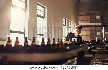 Brewer Looking At Conveyor With Beer Bottles