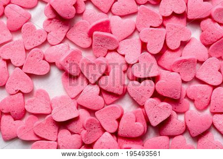 Pink candy hearts scattered on light paper