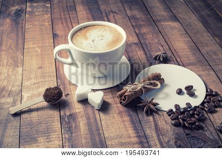 Photo of coffee cup cinnamon sticks coffee beans anise sugar spoon and coasters on vintage wood background. Coffee and spices.