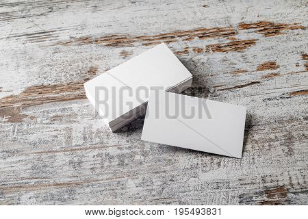 Blank white business cards on vintage wooden background. Mock-up for branding identity. Blank template for design presentations and portfolios.