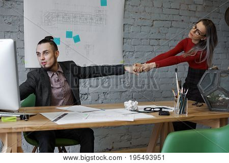 Internet addiction. Overwork concept. Overworked addicted young office worker sitting at desk and working on computer absolutely ignoring attractive female in glasses who is pulling him by the hand