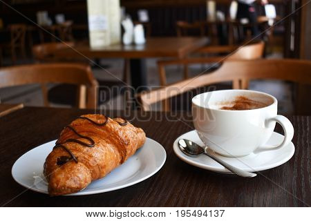 Morning breakfast in the cafe. Croissant with coffee.
