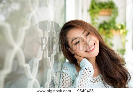 Young asian woman relaxing on a balcony enjoying fresh air. Asian woman enjoying fresh air at home