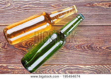 Bottles of beer on old wooden table. Harmful habit to drink alcohol.