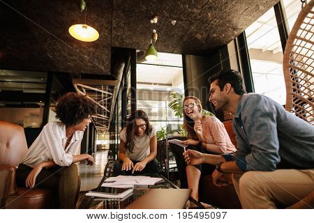 Team of corporate professionals having friendly discussion in a meeting. Multi ethnic business team having project discussion.