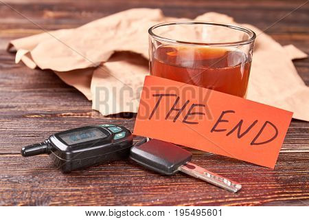 Message the end, alcohol, keys. Glass of alcohol, car keys, note the end on wooden background. Drinking and driving leads to death.