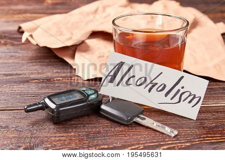 Whiskey glass with car keys. Automobile keys, message alcoholism, glass of alcohol on wooden background. Drunk drivers and death accidents.