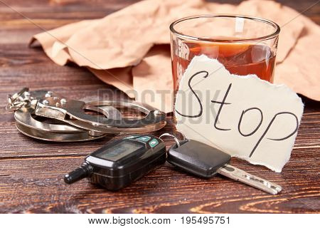 Whiskey with car keys and handcuffs. Message stop, glass of alcohol, metal handcuffs on wooden background. Stop drink and be responsible.