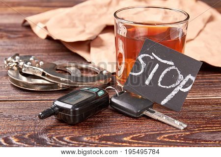Handcuffs, car keys, whisky, paper. Driving keys, metal handcuffs, message stop, whiskey. Hard judgment for road accident.