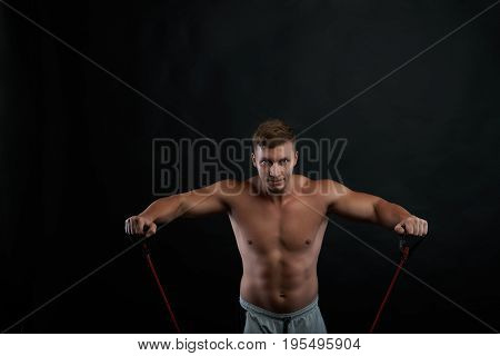 People sports fitness health and active lifestyle concept. Picture of confident determined young athlete strenghtening arms using a rubber band looking at camera with concentrated expression