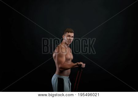 Handsome young Caucasian sportsman with athletic body performing exercises using a resistance band. Portrait of muscular male athlete with naked torso training indoors. Strength and motivation