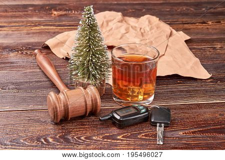 The concept of drink driving. Glass of alcohol beside car keys and gavel on wooden background.