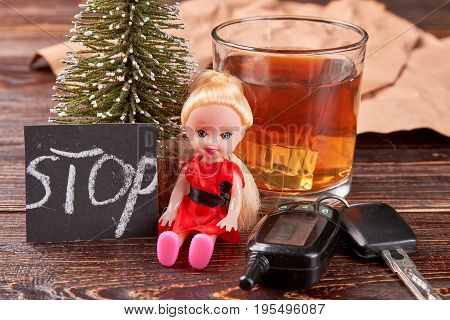 Alcohol beside doll and keys. Metaphor protestation against alcoholism.
