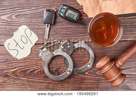Glass of whiskey beside handcuffs. Alcohol drink, gavel, handcuffs, car key, message stop, top view. Booze driving concept.