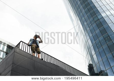 Outdoor shot of unrecognizable stylish male with tattoo wearing oculus rift headset experiencing virtual reality standing on the edge of rooftop with glass windows skyscraper in background