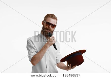 Handsome young bearded businessman in formal shirt and sunglasses holding hat in one hand and microphone in other singing in karaoke. Stylish male performing or recording song standing at white wall