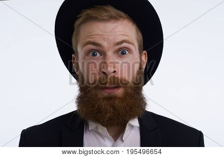 Omg. Indoor shot of surprised stunned young European bearded male dressed in stylish clothing and accessories staring at camera in full disbelief shocked while receiving unexpected astonishing news