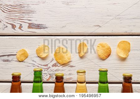 Chips above beer bottlenecks, wooden background. Harmful habits dangerous for life.