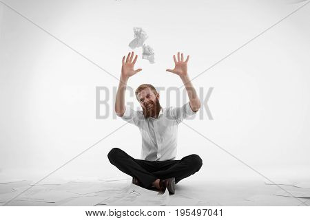 Portrait of frustrated young office worker with thick red beard sitting cross-legged on floor surrounded with papers throwing crumpled paper sheets in air feeling stressed and fed up with paperwork