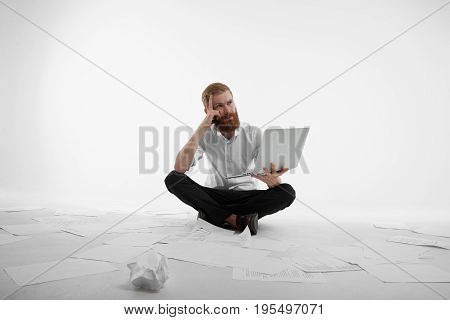 People business job occupation and profession concept. Pensive focused young businessman in formal clothes sitting on floor covered with paper sheets holding laptop pc working on report