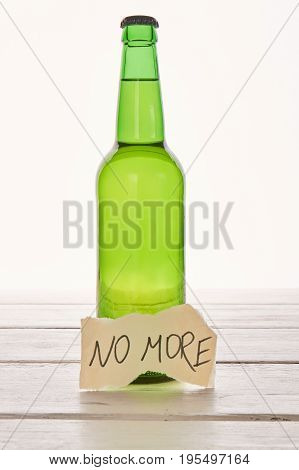 Alcohol liquid leads to death. Transparent bottle of beer, light background.