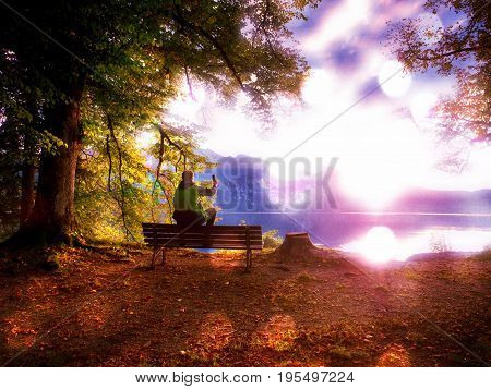 Film Effect. Alone Man Sits Leg Over On Bench Beside An Azure Mountain Lake. Man Relax And Watch Hig