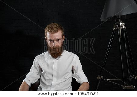 Picture of handsome and confident young male photographer with fuzzy beard relaxing on chair in his studio after photo shooting. People work job occupation profession and creativity concept