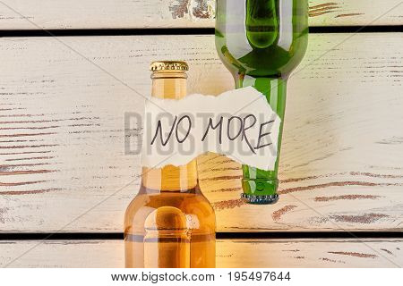 No more alcohol and drunkenness. Message, two bottles, old wooden background.
