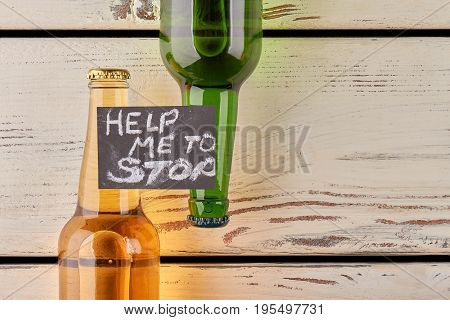 Ways to defeat alcoholism. Written request of help, bottles, old background.