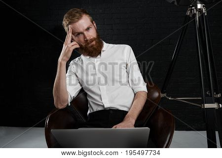 Handsome young European photographer with thick beard sitting on chair in studio with laptop computer retouching pictures after fashion photo shoot looking at camera having tired expression