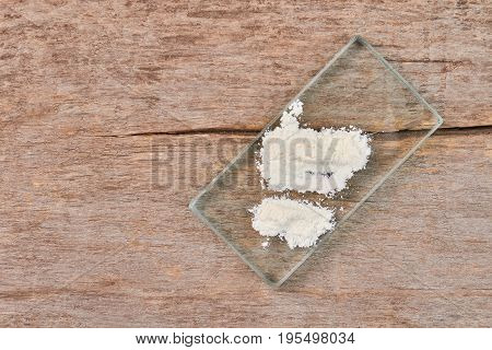 Concept of drugs addiction. White powder on glass, wooden background.