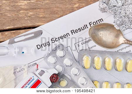 Drug screen result form, pills, ampoule. Paper form test on drugs, pills, spoon, foil, blade, ambulance. Narcotics overdose and medical service.