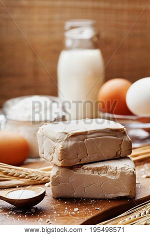 Fresh yeast and ingredients for baking on kitchen table. Product for preparing pizza or bread.
