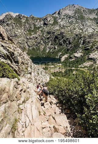 LAC DE MELO NEAR CORTE CORSICA - JULY 2017. Hikers on rocky trail between Lac de Capitello and Lac de Melo in Corsica on a sunny July day