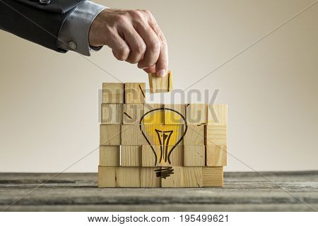 Businessman Arranging Wooden Blocks Forming A Yellow Light Bulb