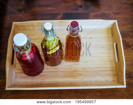 Three bottles of homemade kombucha tea on a bamboo tray. Rustic wood table. Rasberry mint apple and orange blossom flavors.