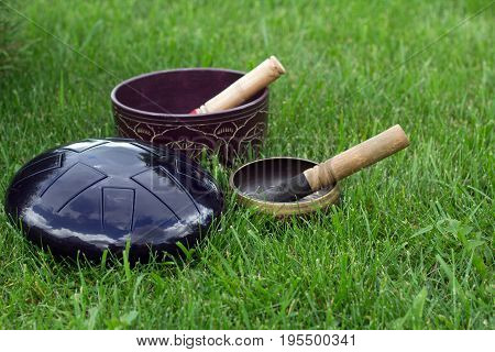 Two Tibetan Singing Bowls With Sticks And Handpan On Green Grass