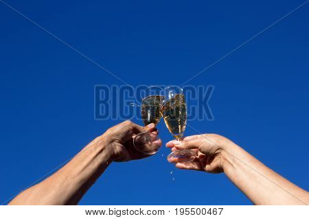 Hands Of Man And Woman Clink Wineglasses Of Sparkling White Wine On Blue Sky