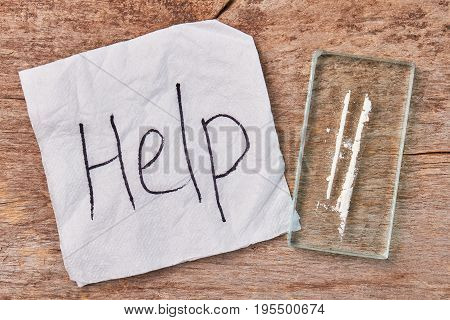 Text help, narcotics, wooden background. Drugs dependence need of professional support.