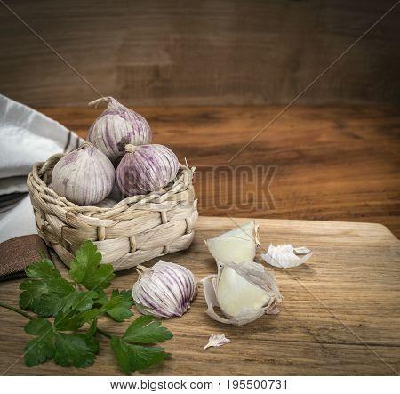 Garlic. Garlic in a wicker basket, parsley on chopping block.